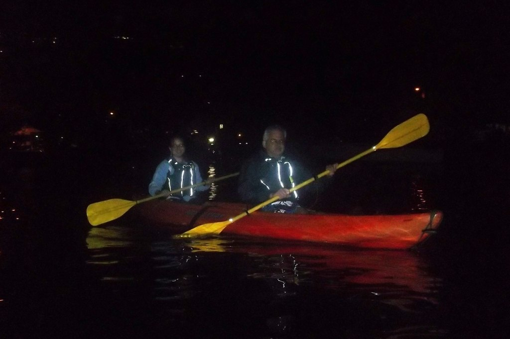 two adults kayaking in the dark