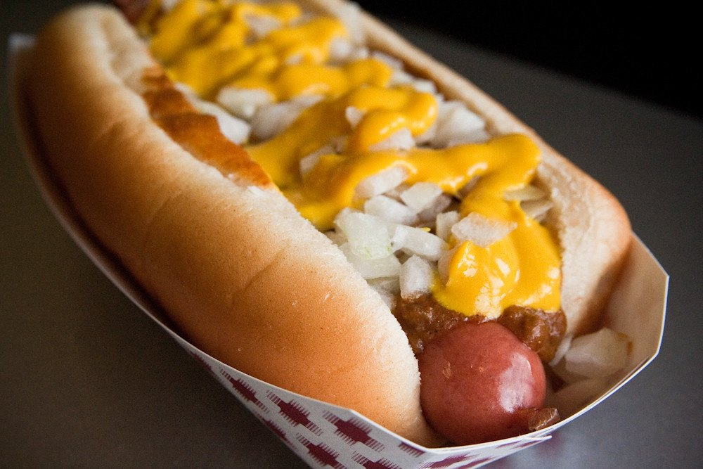 hot dog topped with mustard, meat sauce, and raw onion better known as a detroit coney dog