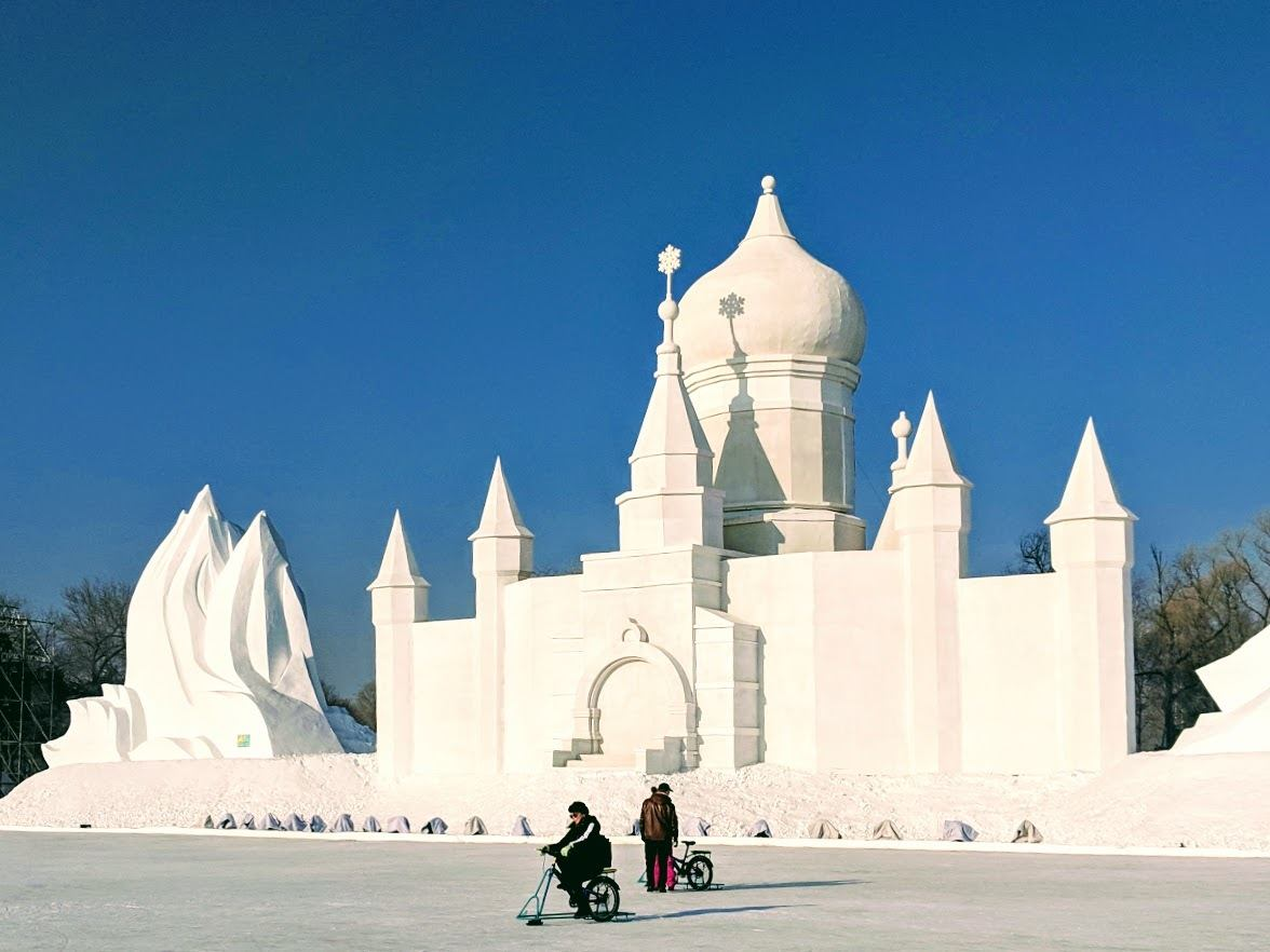 Ice biking in front of massive snow sculptures in Harbin China