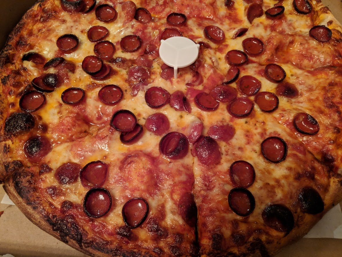 close up of pizza with cup and curl pepperoni