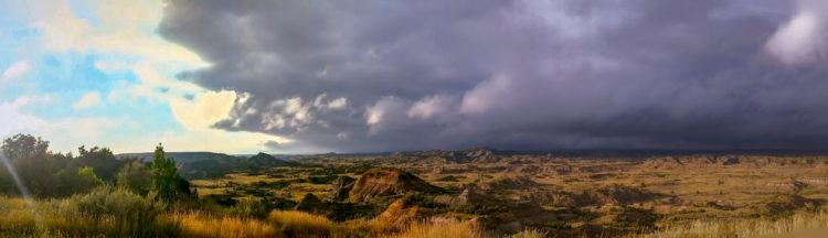 painted canyon (trnp) with sunshine on one side and storm clouds on the other