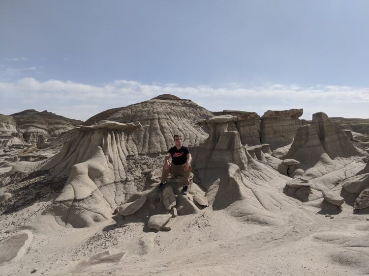 posing with rock formations in new mexico badlands