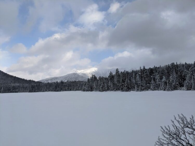 frozen lonesome lake with mountain summit in background