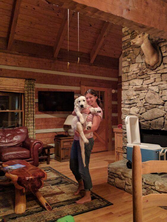 girl holding dog in cabin
